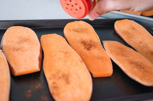 sprinkling cinnamon on sweet potatoes